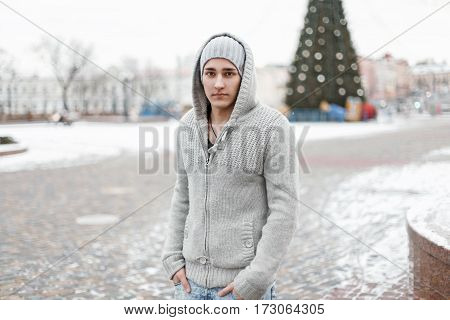 Handsome Stylish Man In Fashionable Knitted Sweater On A Background Of A Winter City.