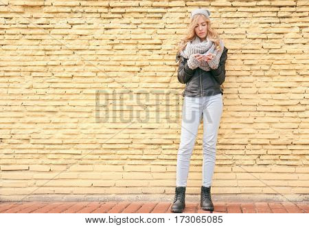 Young beautiful woman with smartphone standing on yellow brick wall background