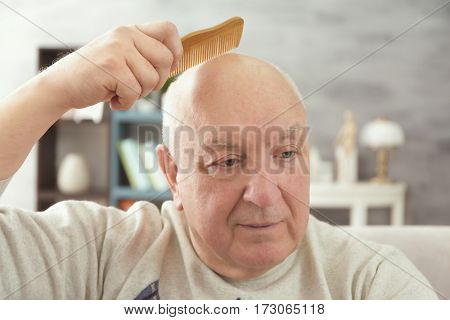 Senior bald man with comb at home