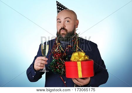 Funny fat man with birthday present and glass of champagne on color background
