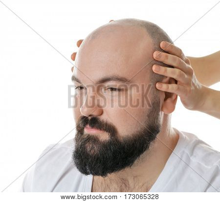 Female hands touching head of bald adult man on white background