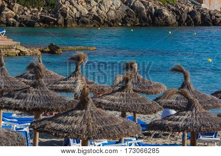 Blue sea and sand beach with sun loungers and parasols.