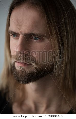Portrait of man with long blond hair. Closeup portrait of young boy. Brutal bull with amazing eyes