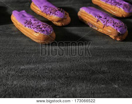 Delicious glazed eclairs on dark textured background