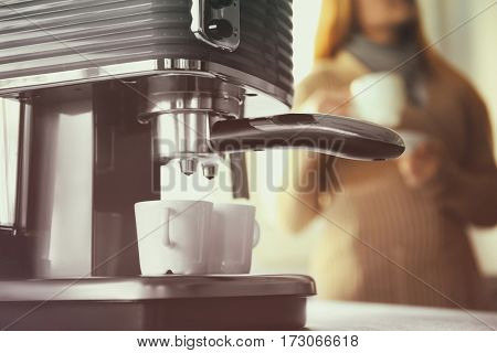 Closeup of making aromatic espresso in coffee machine and woman on background