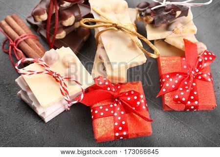 Composition of chocolate pieces and small presents on grey background
