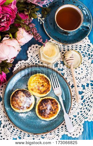 Cottage cheese fritters, honey and tea in a vintage cup on a blue background. Studio Photo