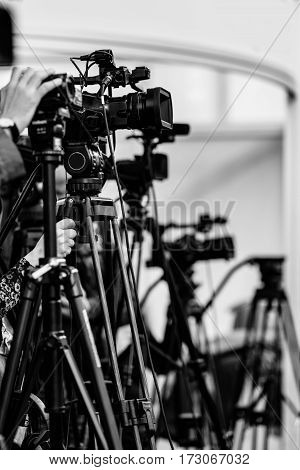 Video camera recording press conference, black And white