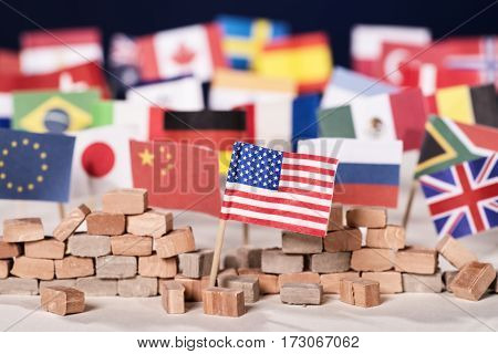 American flag in front of a wall and flags of other countries