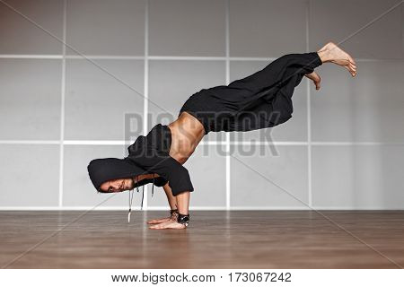 Handsome Man In Black Clothes Dancing On The Floor. Man Stands On Hands