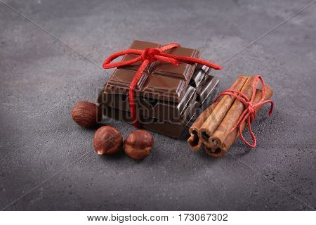 Chocolate pieces with nuts and cinnamon sticks on grey background