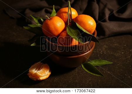Bowl with tangerines on dark background
