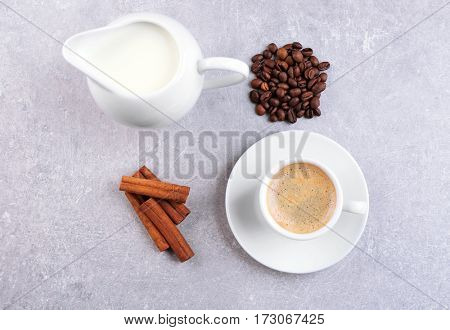 Fresh coffee with ingredients on grey background