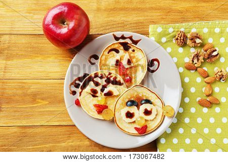 Creative pancakes on wooden background