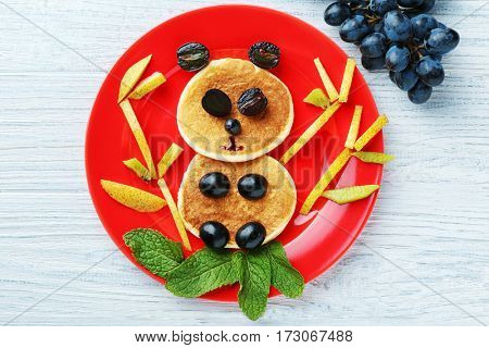 Plate with creative homemade pancakes on wooden table