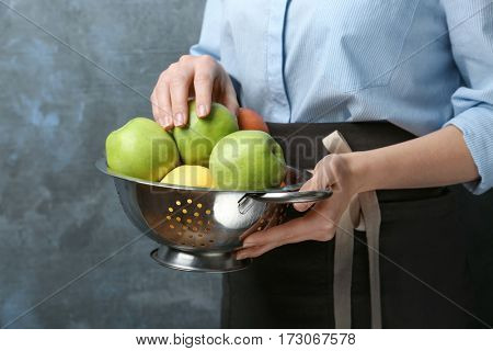 Young woman in apron holding colander with juicy apples, closeup