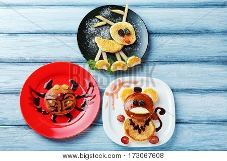 Plates with creative homemade pancakes on wooden table
