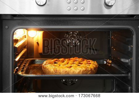 Delicious pie with fruits on baking tray in oven