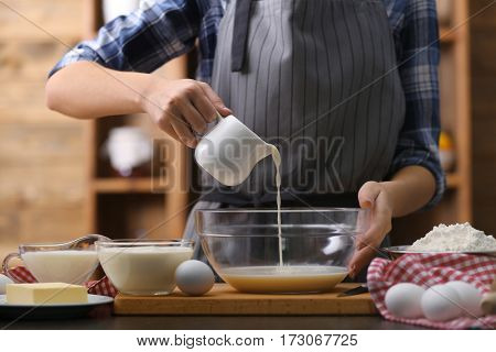 Cooking concept. Woman making dough on kitchen