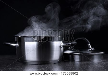 Pan with steam on dark background