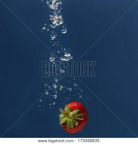 Fresh juicy strawberry falling in water on dark background