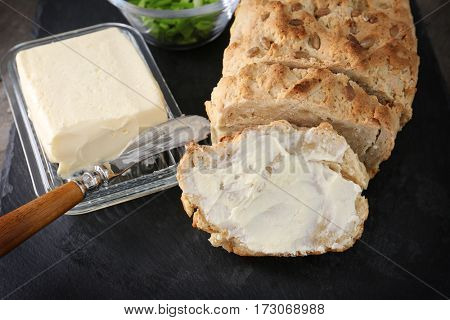 Sliced loaf of beer bread with butter on slate plate