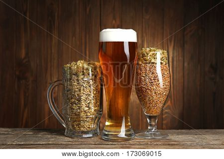 Glasses of beer and seeds on wooden background