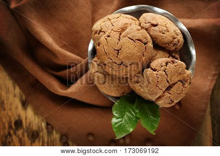 Bowl with delicious cookies on brown napkin