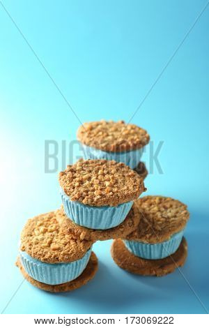 Pile of tasty kiwi ice cream cookie sandwiches on blue background