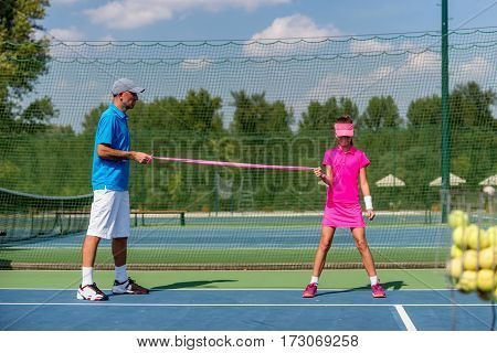 Tennis girl with resistance band, toned image, outdoors, selective focus