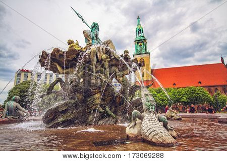 BERLIN GERMANY - JUNE 6: Neptune fountain and St. Mary's Church known in German as Marienkirche near Alexanderplatz in Berlin in 2012