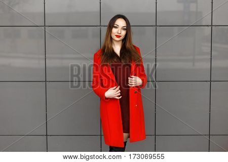 Beautiful Fashionable Girl In A Red Elegant Coat Near The Gray Wall
