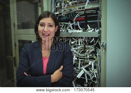 Portrait of technician standing with arms crossed in server room