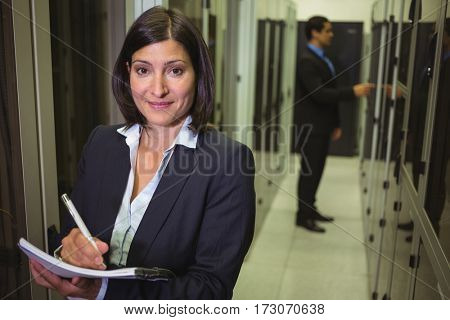 Technician maintaining record of rack mounted server in paper in server room