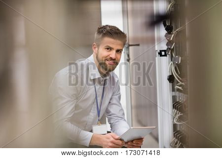 Portrait of technician using digital tablet while analyzing server in server room