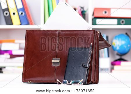 Brown leather briefcase on table at office