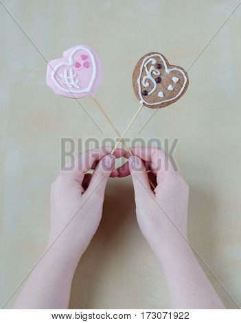 Woman's hands holding a Valentine cookies. Handmade work