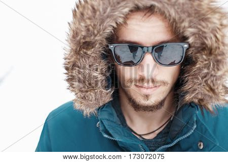 Stylish Man Tourist In Alaska Jacket With A Hood And Sunglasses On A White Background