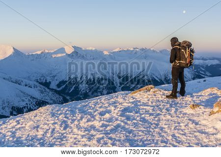 Hiker With Backpack Admiring Mountain Views In Winter.