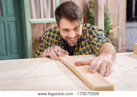 Smiling bearded carpenter measuring wooden plank on table