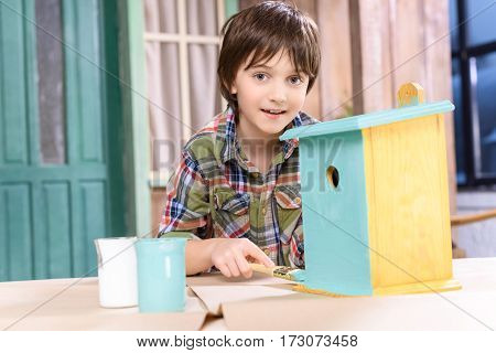 Cute little boy painting wooden birdhouse and smiling at camera