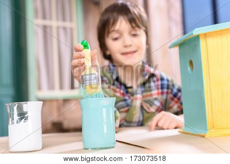Cute smiling boy holding paintbrush while painting handmade birdhouse