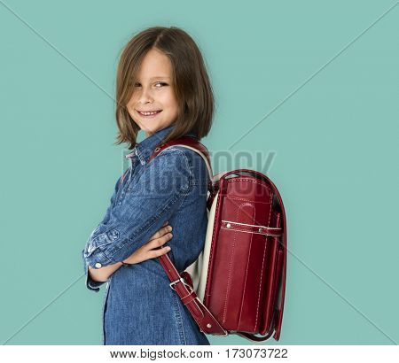 A girl with backpack is smiling.