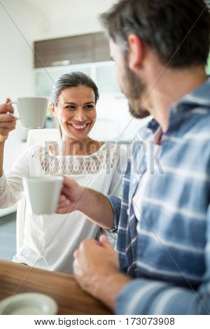 Couple interacting while having coffee at home