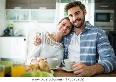 Portrait of couple sitting with arm around while having breakfast at home