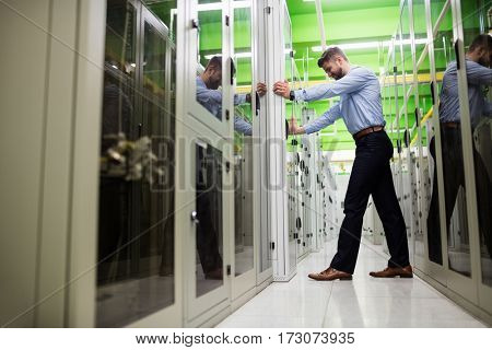 Technician adjusting server cabinet in server room