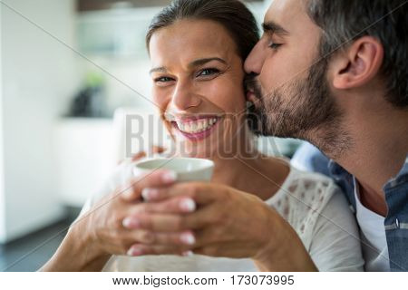 Man kissing woman on cheeks while having coffee at home