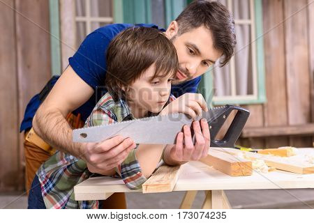 Pensive father and son leaning on wooden table and inspecting hand saw