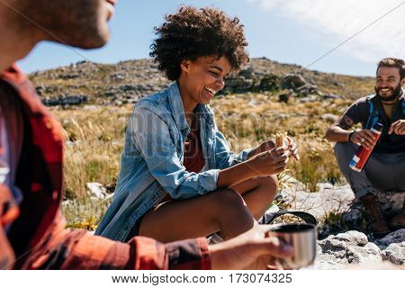 happy young woman with friends taking a break during hike in countryside. Group of people relaxing and eating during hike.