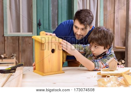 Concentrated father and son making wooden birdhouse together in workshop